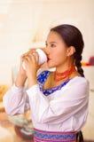 Mujer bastante joven que lleva la blusa andina tradicional, colocando el café para arriba de consumición de la taza blanca Imagen de archivo