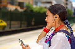 Mujer bastante joven que lleva la blusa andina tradicional y la mochila azul, para autobús que espera en la plataforma de la esta Fotografía de archivo