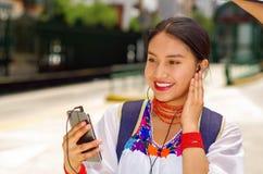 Mujer bastante joven que lleva la blusa andina tradicional y la mochila azul, para autobús que espera en la plataforma de la esta Fotografía de archivo libre de regalías
