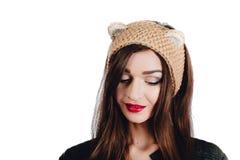 Mujer bastante joven que lleva un sombrero beige tejido a mano en el fondo blanco Aislado Muchacha hermosa adentro con la aleta d Foto de archivo