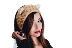 Mujer bastante joven que lleva un sombrero beige tejido a mano en el fondo blanco Aislado Muchacha hermosa adentro con la aleta d Foto de archivo libre de regalías