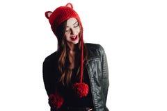 Mujer bastante joven que lleva un sombrero rojo tejido a mano en el fondo blanco Aislado Muchacha hermosa adentro con la aleta de Foto de archivo libre de regalías