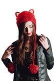 Mujer bastante joven que lleva un sombrero rojo tejido a mano en el fondo blanco Aislado Muchacha hermosa adentro con la aleta de Foto de archivo