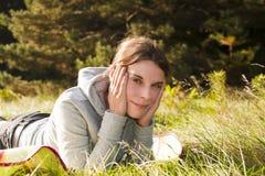 Mujer bastante joven que miente en hierba Fotografía de archivo libre de regalías