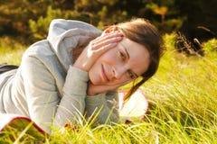 Mujer bastante joven que miente en hierba Imagen de archivo