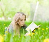 Mujer bastante joven que miente en hierba con los dientes de león y que lee un libro Imágenes de archivo libres de regalías