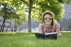 Mujer bastante joven que miente en la hierba con el libro Fotografía de archivo
