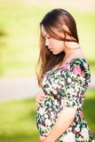 Mujer bastante joven que mira abajo de adorar su estómago embarazada en un fondo verde hermoso del parque Fotografía de archivo