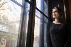 Mujer bastante joven que mira hacia fuera la ventana Fotos de archivo libres de regalías