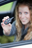 Mujer bastante joven que muestra apagado su coche de la marca de fábrica Foto de archivo libre de regalías