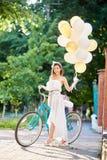 Mujer bastante joven que presenta con el ballong colorido cerca de la bici azul en el callejón del parque imagenes de archivo