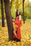 Mujer bastante joven que presenta en parque del otoño Foto de archivo libre de regalías