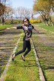 Mujer bastante joven que salta en hierba verde Imagen de archivo libre de regalías