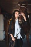 Mujer bastante joven que se coloca en el granero que abraza su caballo Imagen de archivo libre de regalías