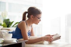 Mujer bastante joven que se relaja en el sofá con el libro Imagen de archivo libre de regalías