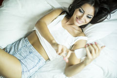 Mujer bastante joven que se relaja en la cama Imagenes de archivo