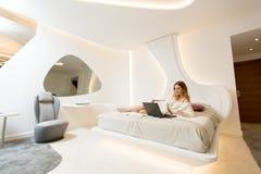 Mujer bastante joven que se relaja en una cama con el ordenador portátil Fotos de archivo