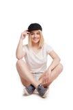 Mujer bastante joven que se sienta con las piernas cruzadas aisladas Foto de archivo
