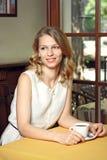 Mujer bastante joven que se sienta en el café con una taza de café Imágenes de archivo libres de regalías