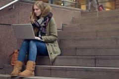 Mujer bastante joven que se sienta en pasos en ciudad Foto de archivo