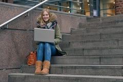Mujer bastante joven que se sienta en pasos en ciudad Fotografía de archivo libre de regalías
