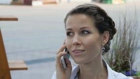 Mujer bastante joven que sonríe mientras que llama alguien a través del teléfono móvil Fotos de archivo libres de regalías