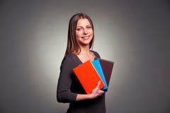 Mujer bastante joven que sostiene los libros Fotos de archivo libres de regalías