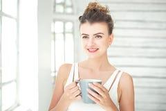 Mujer bastante joven que sostiene una taza de café Fotografía de archivo libre de regalías