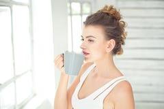 Mujer bastante joven que sostiene una taza de café Foto de archivo libre de regalías
