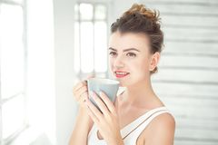 Mujer bastante joven que sostiene una taza de café Imagen de archivo