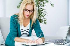 Mujer bastante joven que trabaja con el ordenador portátil en casa Imagenes de archivo
