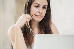 Mujer bastante joven que trabaja en el ordenador portátil en la oficina Foto de archivo