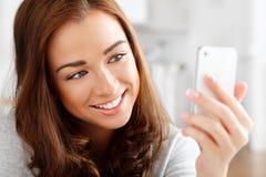 Mujer bastante joven que usa el teléfono móvil Imágenes de archivo libres de regalías