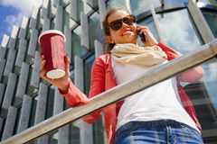 Mujer bastante joven que usa el teléfono móvil que sostiene la taza del coffe Foto de archivo