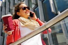 Mujer bastante joven que usa el teléfono móvil que sostiene la taza del coffe Fotografía de archivo