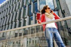 Mujer bastante joven que usa el teléfono móvil que sostiene la taza del coffe Fotos de archivo libres de regalías