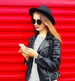 Mujer bastante joven que usa smartphone en estilo de la roca del negro de la moda sobre rojo colorido Fotografía de archivo libre de regalías