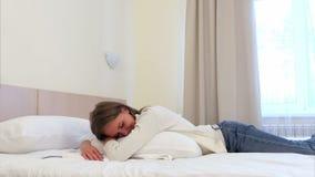 Mujer bastante joven relajada que duerme en la cama blanca en la habitación metrajes