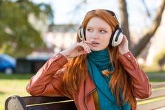 Mujer bastante linda que escucha la música usando los auriculares Imagenes de archivo