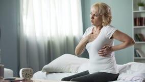 Mujer bastante madura que se sienta en cama y que sufre del ataque del corazón, salud fotografía de archivo libre de regalías
