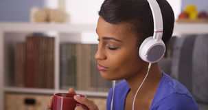 Mujer bastante negra que escucha la música con los auriculares Imagenes de archivo