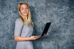 Mujer bastante rubia con el ordenador portátil en un fondo gris Fotos de archivo