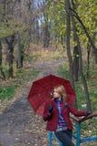 Mujer bastante rubia con el paraguas en las manos que presentan en el puente Imagenes de archivo
