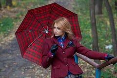 Mujer bastante rubia con el paraguas en las manos que presentan en el puente Imagen de archivo