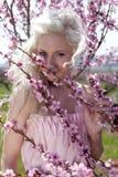 Mujer bastante rubia de los jóvenes en jardín floreciente imagenes de archivo