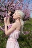 Mujer bastante rubia de los jóvenes en jardín floreciente Imagen de archivo