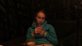 Mujer bastante rubia de los jóvenes que usa el app en la bebida de consumición del smartphone en café metrajes