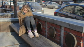Mujer bastante rubia de los jóvenes que usa el teléfono móvil que goza del sol y del viento en la calle de la ciudad almacen de video