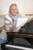 Mujer bastante rubia que canta por un piano Foto de archivo libre de regalías