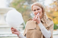 Mujer bastante rubia que come la seda del caramelo Fotos de archivo libres de regalías